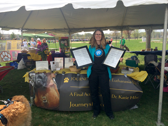 Vet Katie Hilst holding up framed pet tributes that she walked with for Puppy Up 2015