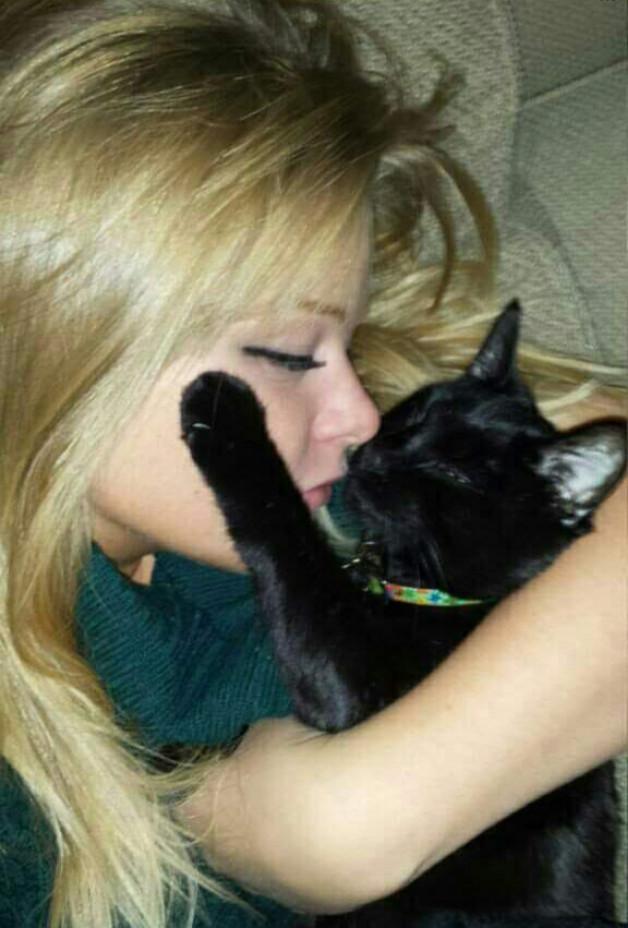 blond girl and black cat snuggling blond girl and black cat snuggling